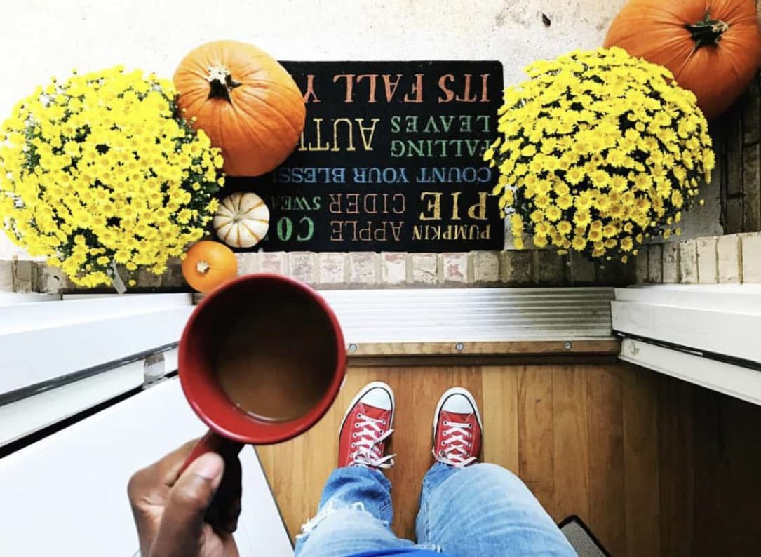 Photo of fall porch decor with coffee and mums and pumpkins.