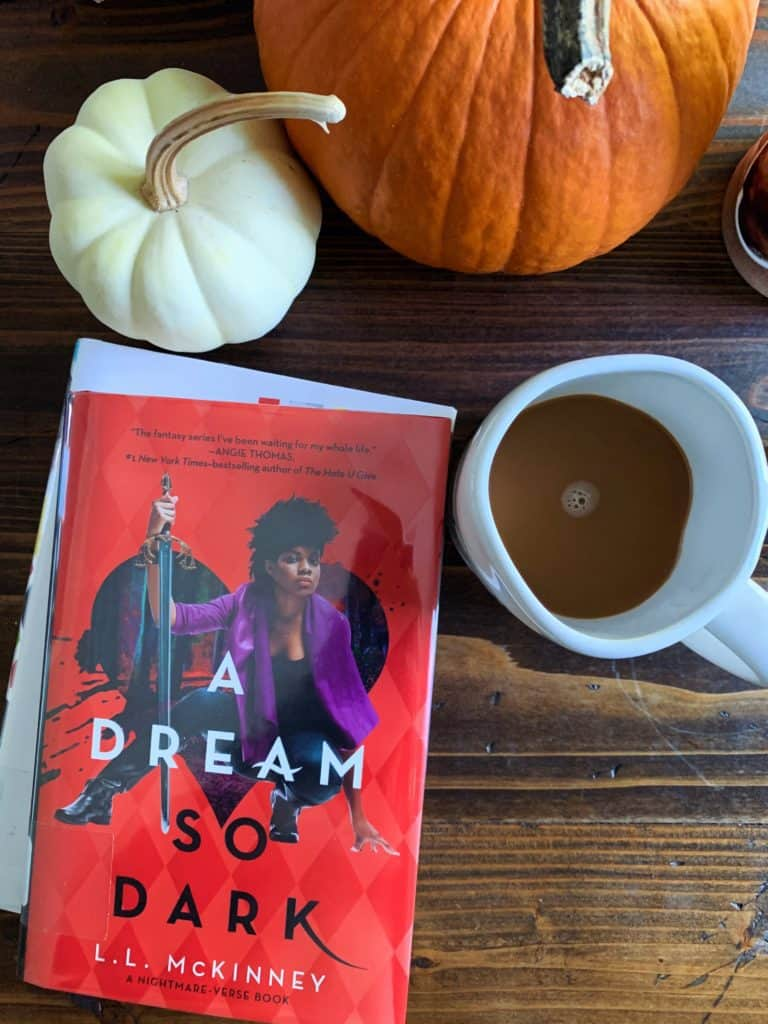 There are pumpkins coffee and a book A Dream So Dark on the table.