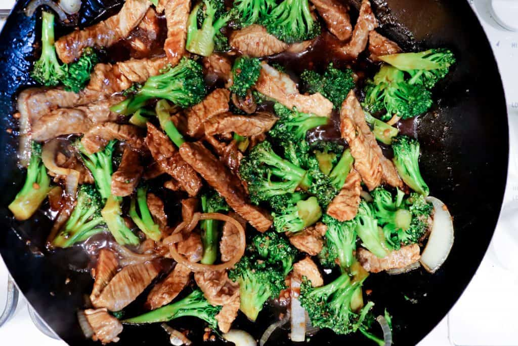 gluten free beef and broccoli being cooked in a wok